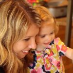 Toddler Emma is hugged by her mom